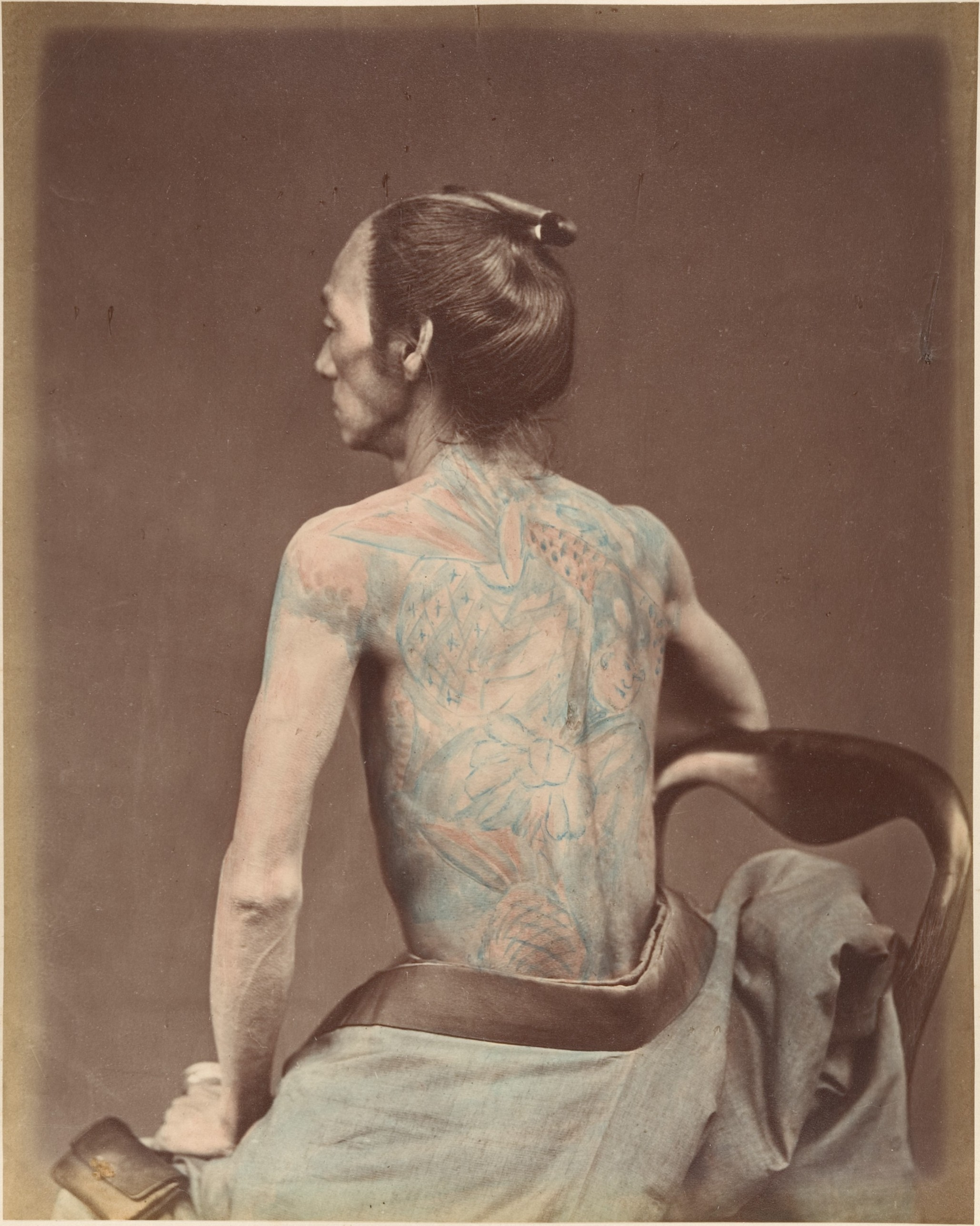 photograph, black and white with colorisation, man with back tattoo