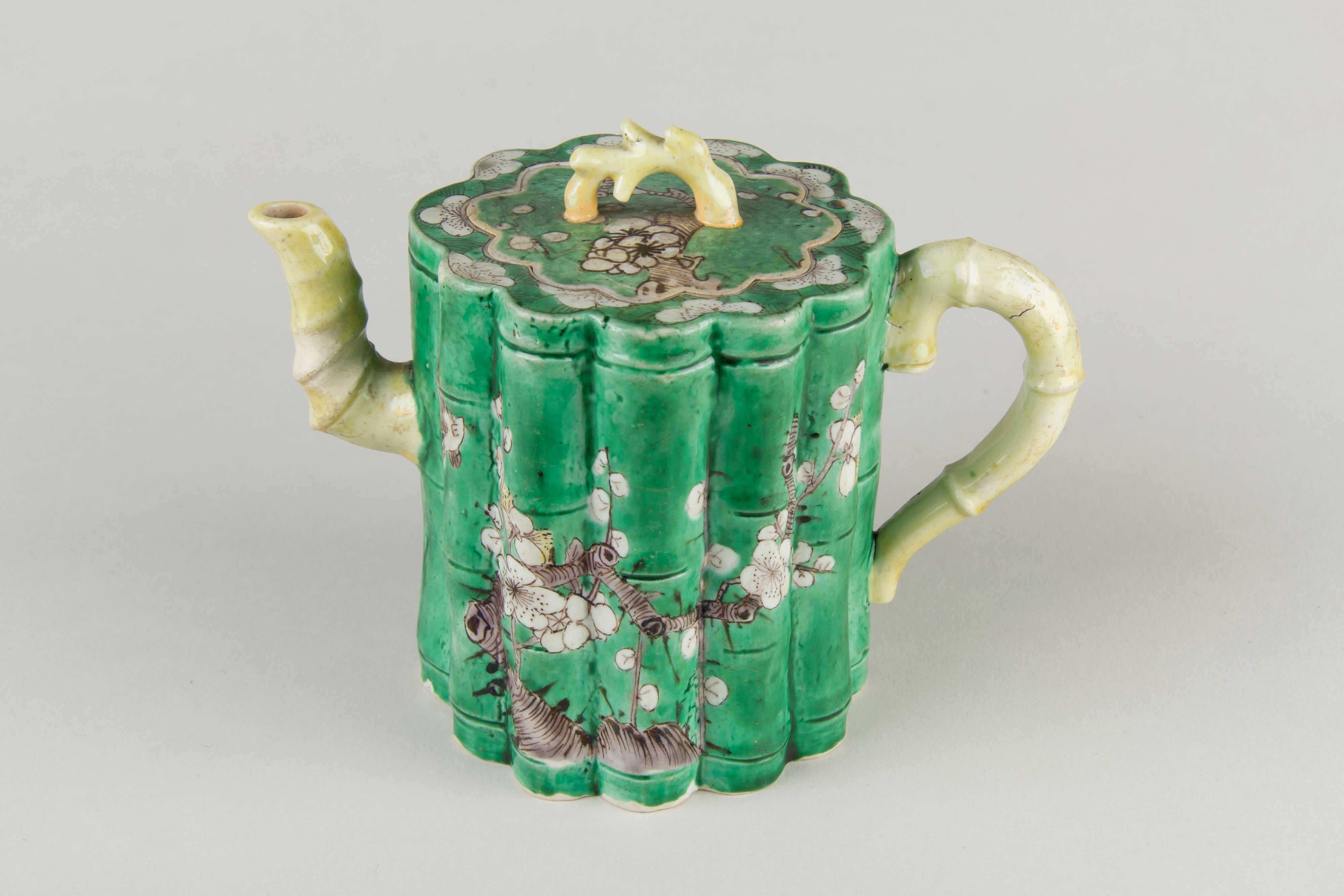 green teapot with floral design