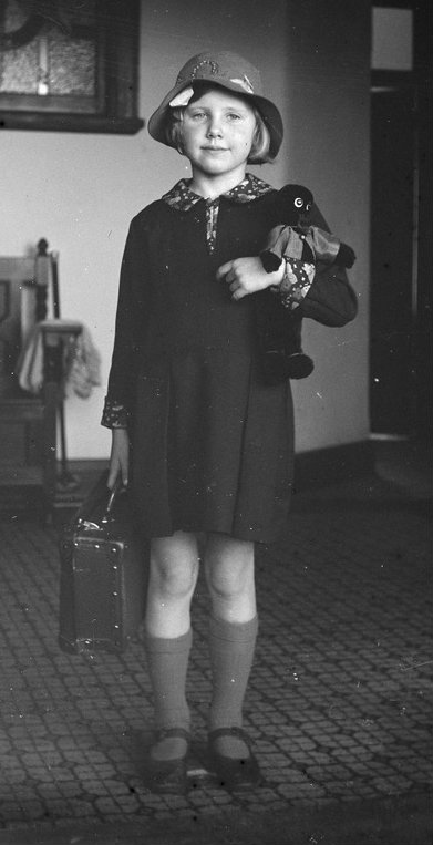 Photograph, Margaret in school uniform. Girl, whole-length, standing in doorway, dressed in school uniform, holding school case and a soft toy.