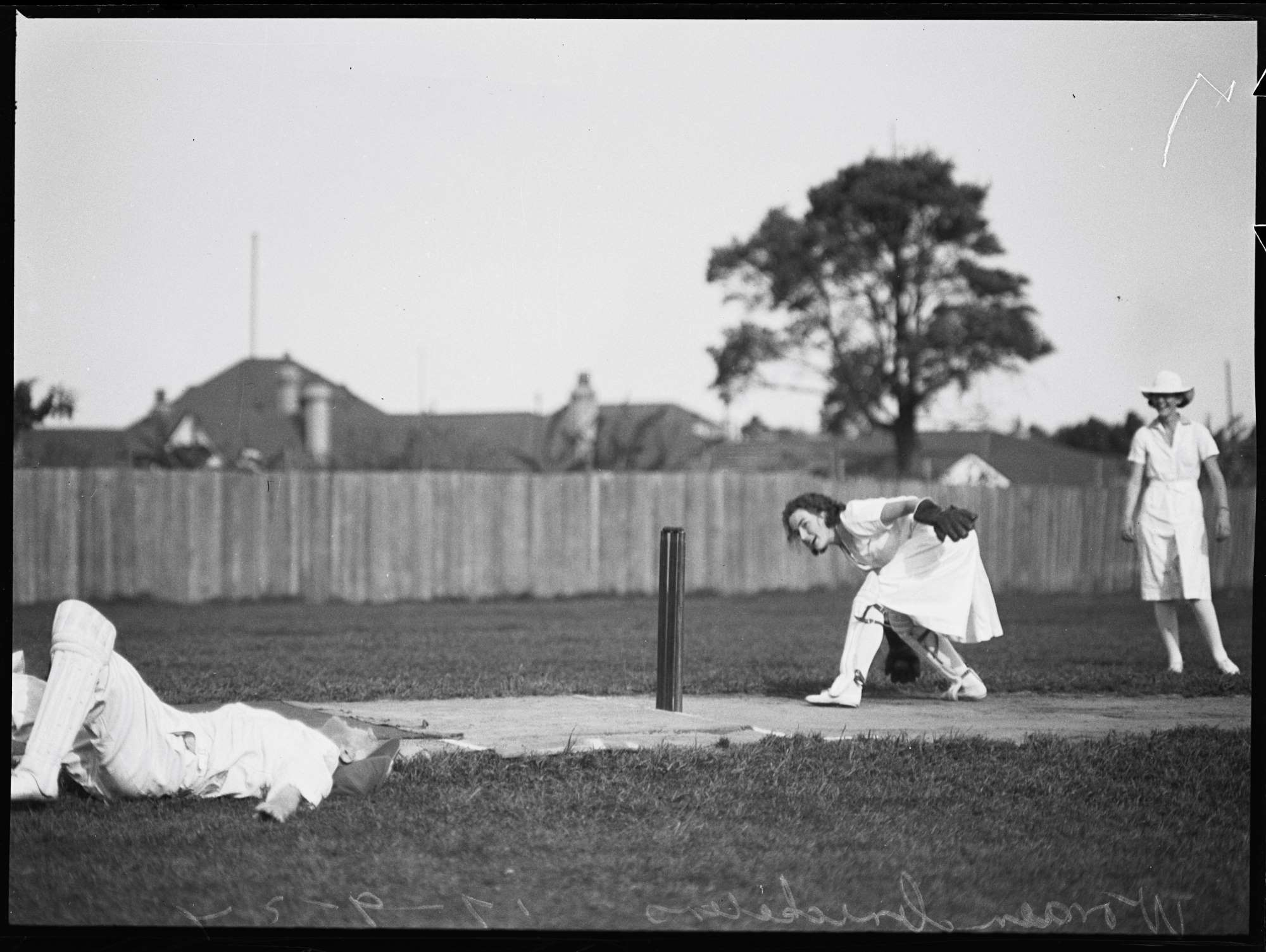 Female cricketer lying on ground as another cricketer stands at the stumps