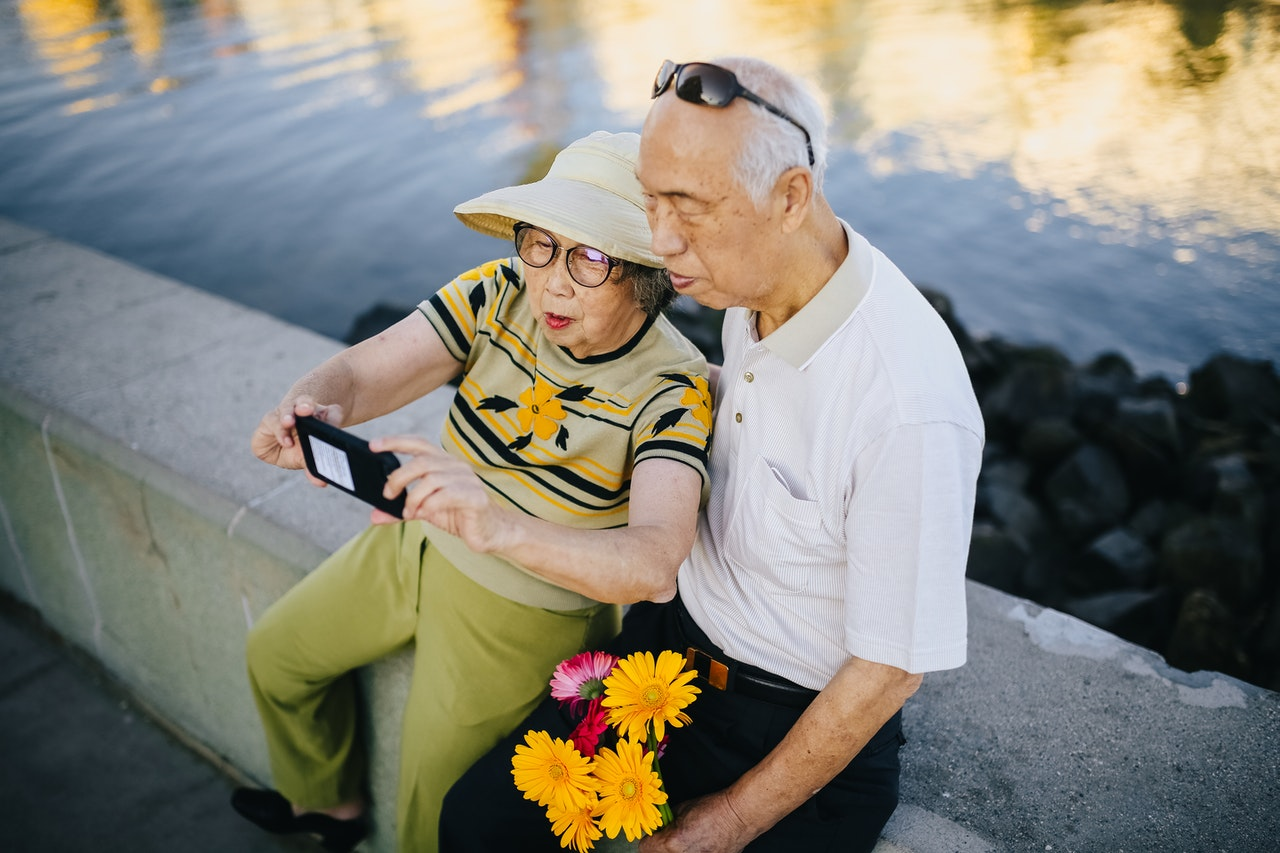 2 older people smiling and taking a selfie on a mobile phone