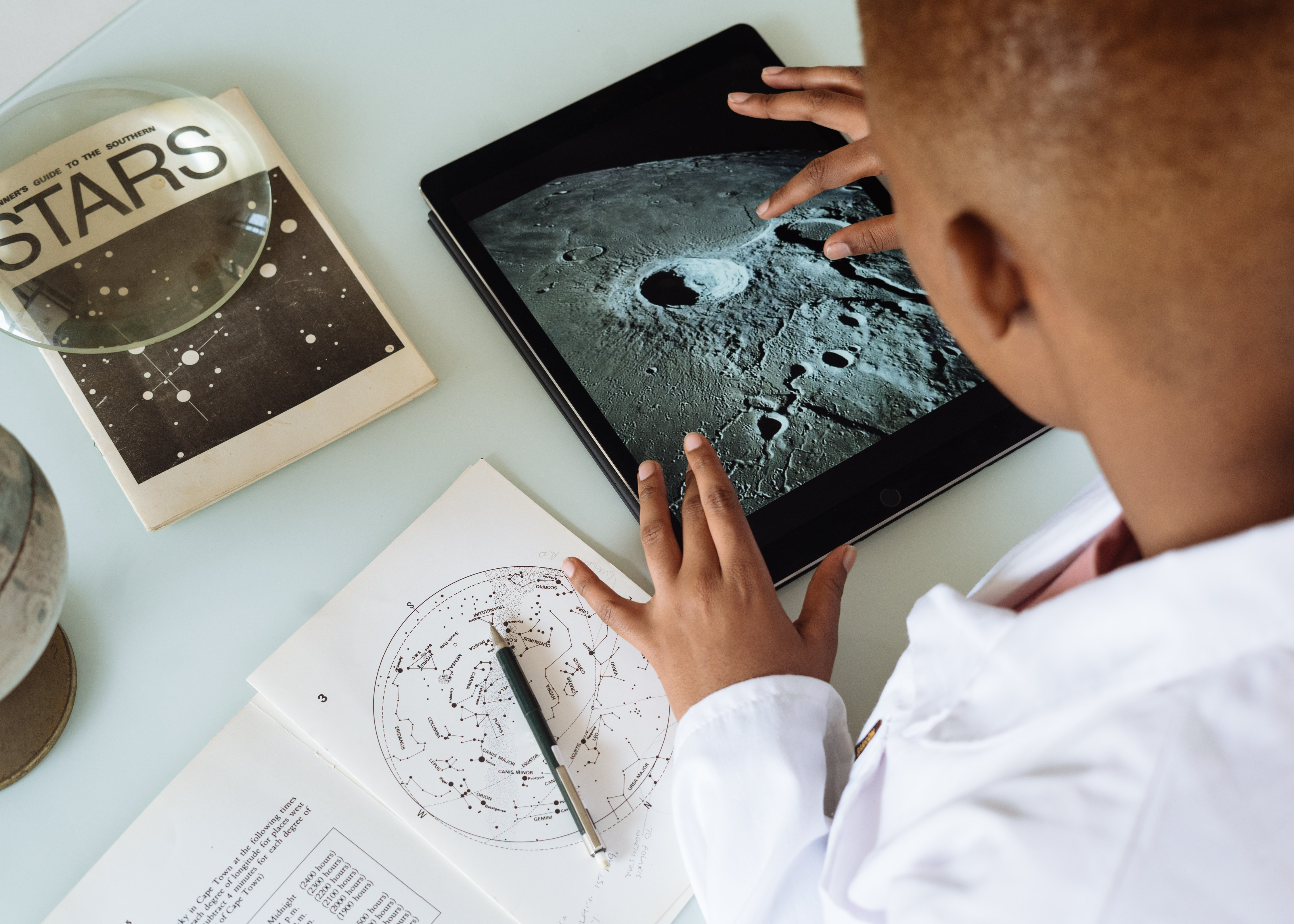 Photo of young man studying images of the moon