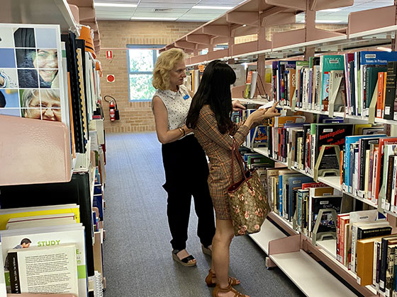 student and librarian searching for book