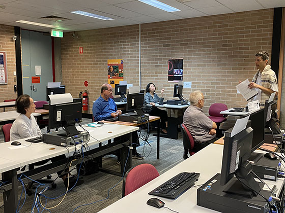 students attending technology class in library
