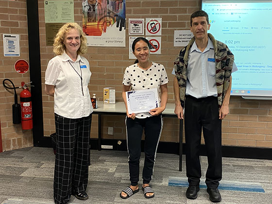 student with certificate and librarians