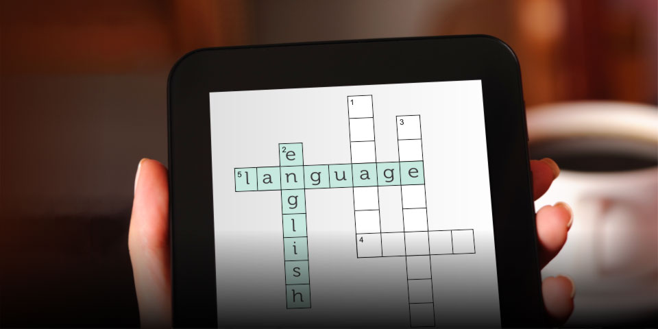 Hand holding a smartphone with a crossword on screen showing the words English language.