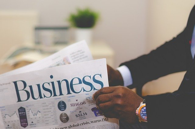 man in a suit holds a newspaper with Business as a headline