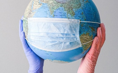 World globe wearing a mask being held up by gloved hands