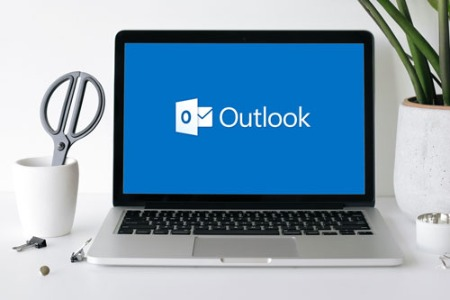 Laptop on a desk with MS Outlook icon on screen