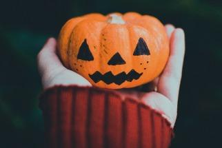 Person holding small Halloween Jack-O-Lantern