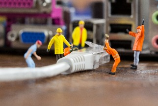 Plastic toy workers fixing cable