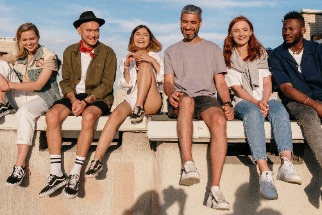 Group of smiling people sitting on a wall on a sunny day