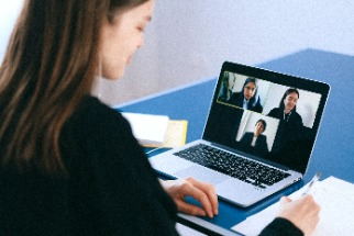 Person on a laptop with online meeting on screen.